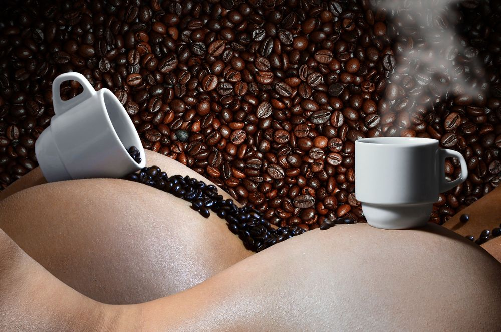 A photograph of two white cups of hot coffee with lots of coffee beans, which lie on two beautiful and sexy naked female bodies. Erotic photo about the use of coffee drinks