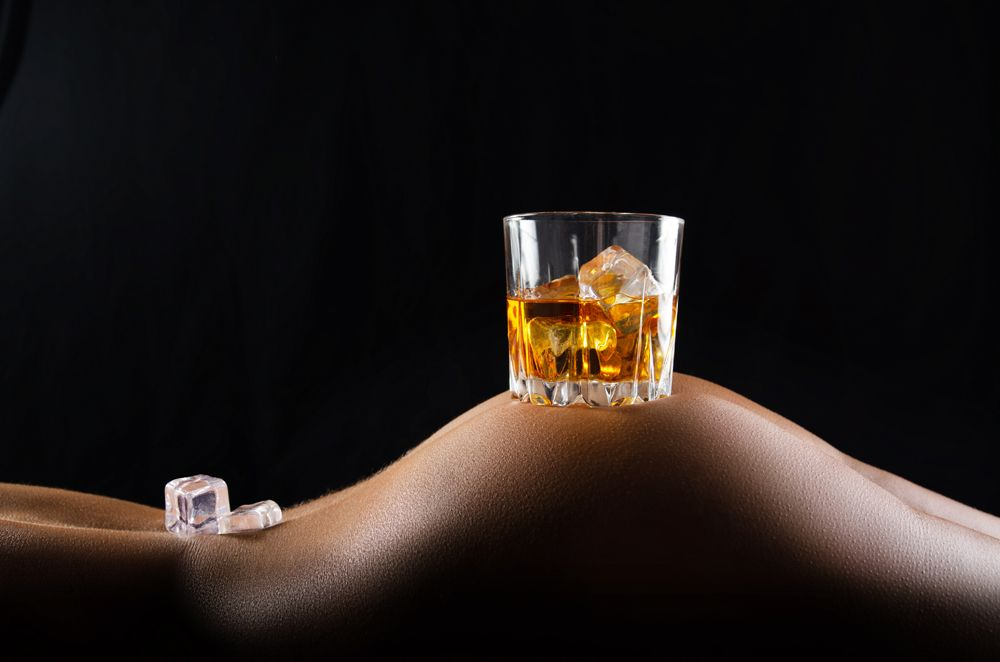 Caucasian laying down model holds glass of whiskey with icecubes